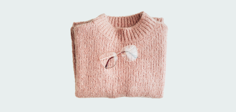Flat lay of glasses on a pink wool knitted jumper